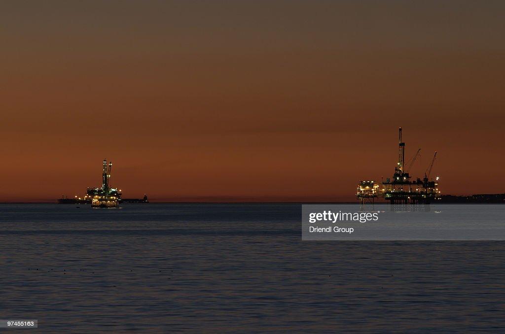 Ocean Oil Derricks at Dusk : Stock Photo