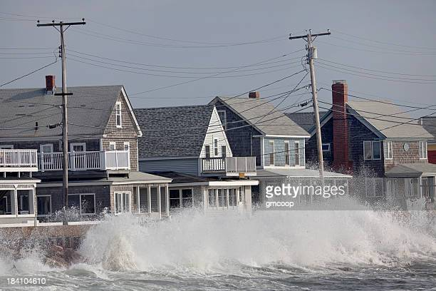Ocean Storm Waves Crashing into Seawall in front of Houses