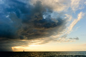 Ocean sunset sailboat storm clouds is a powerful cloudscape with sun rays bursting over the open sea.