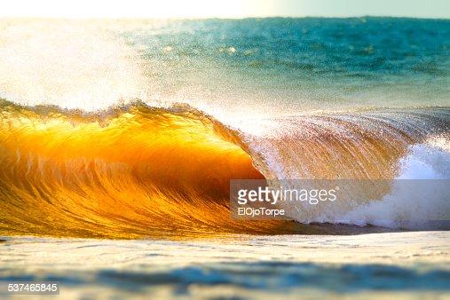 Ocean wave breaking at sunset