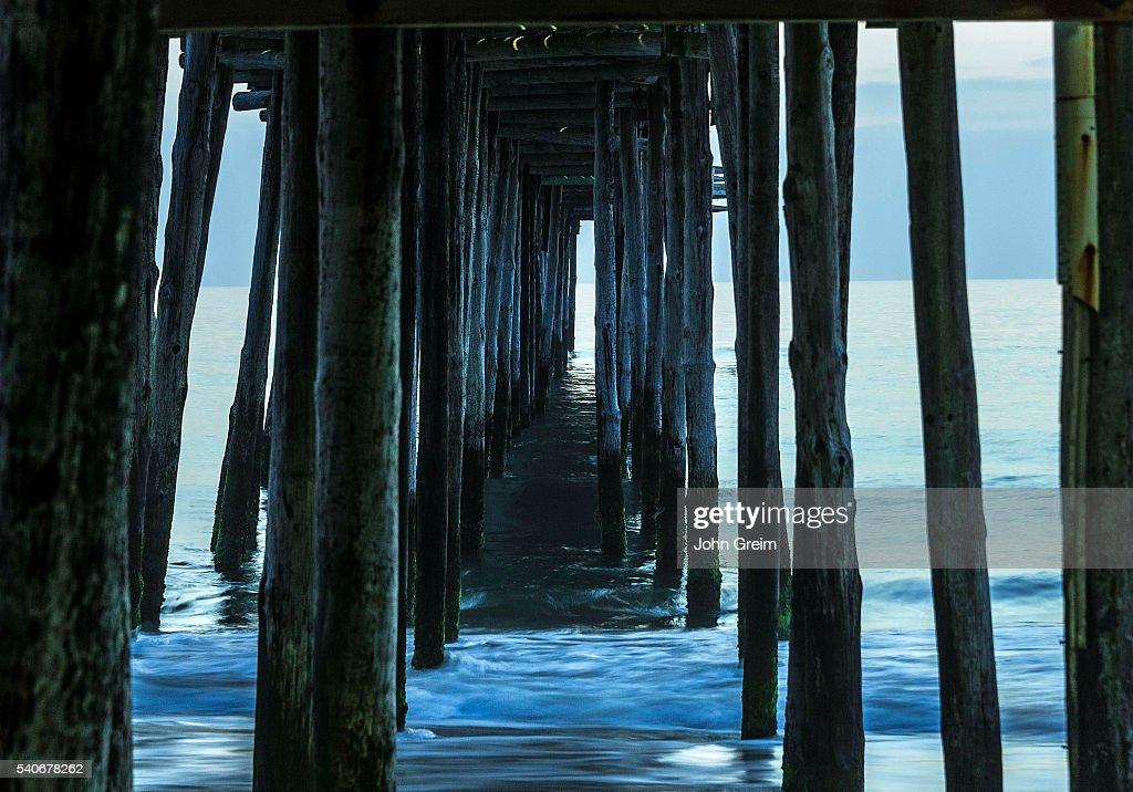 Ocean waves under a fishing pier