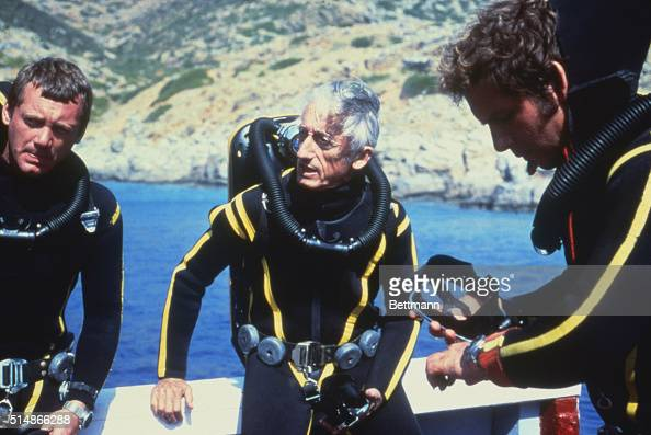 Oceanographer Jacques Cousteau and colleagues prepare for a dive wearing wet suits and scuba gear