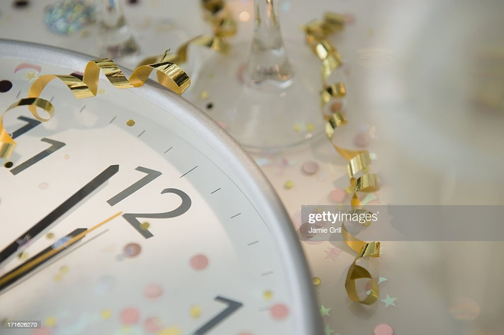12 o'clock on clock decorated with confetti and streamer