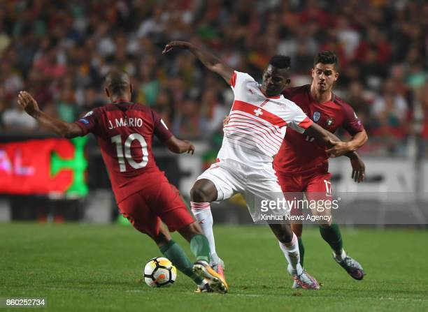 LISBON Oct 11 2017 Joao Mario and Andre Silva of Portugal vies with Breel Embolo of Switzerland during the FIFA World Cup 2018 Qualifiers Group B...