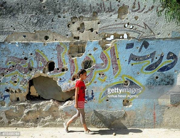 DAMASCUS Oct 17 2016 A Palestinian girl walks by a wall with bullet holes in the Sayyida Zaynab camp for Palestinian refugees in Sayyida Zaynab town...