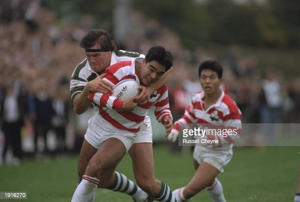 Catterill of Zimbabwe tackles Terunori Masuho of Japan during the 1991 Rugby Union World Cup match in Belfast Northern Ireland Japan won the game 528...