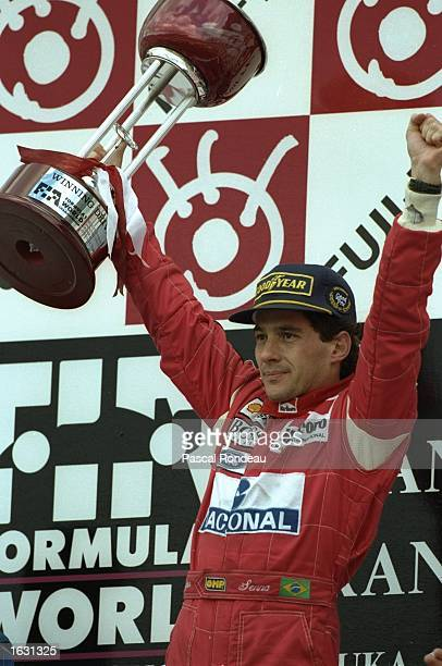 McLaren Ford driver Ayrton Senna of Brazil holds the trophy aloft after his victory in the Japanese Grand Prix at the Suzuka circuit in Japan...