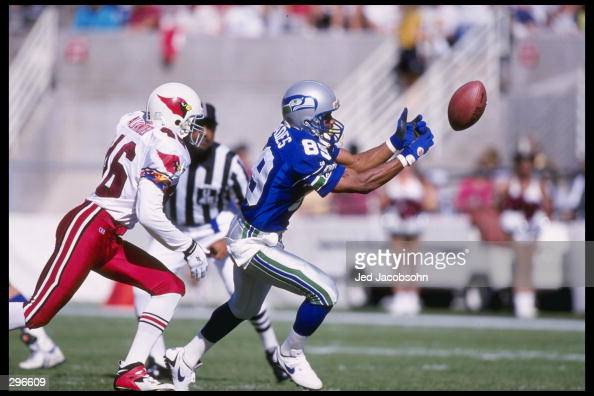 Wide receiver Brian Blades of the Seattle Seahawks tries to catch the ball as defensive back Brent Alexander of the Arizona Cardinals chase him at...