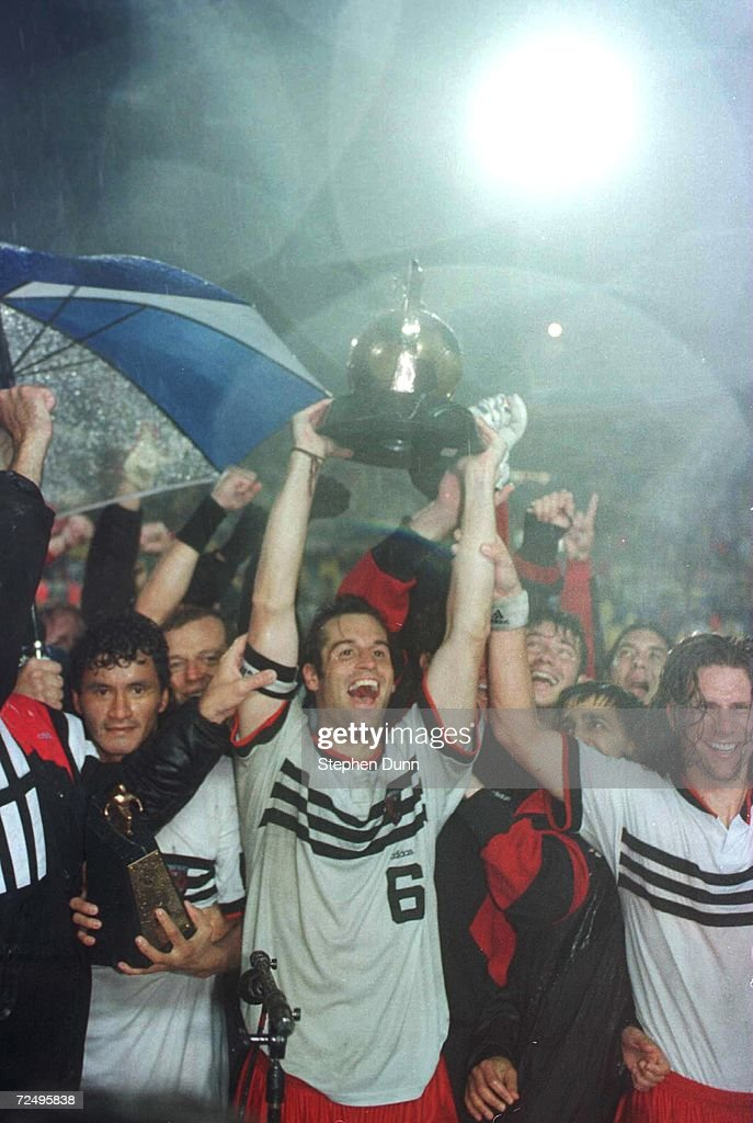 John Harkes and his teammates of DC United celebrate capturing the Alan I Rothenberg Cup after their team defeated the Los Angeles Galaxy in the...