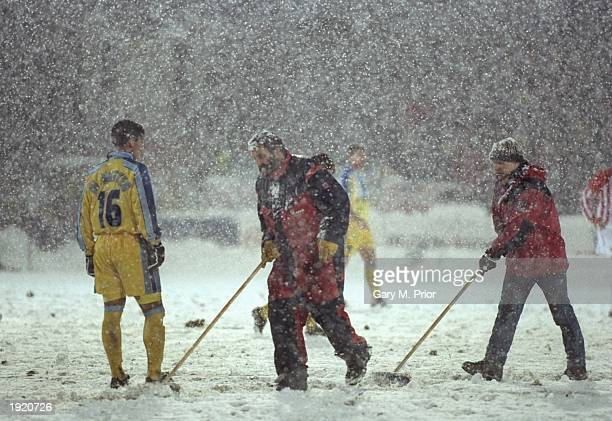 Groundsmen sweep the snow ridden pitch during the European Cup Winners Cup first leg match between Tromso and Chelsea at Tromso in Norway Tromso won...