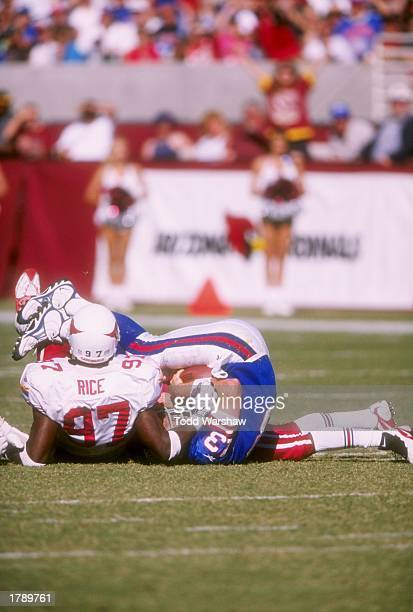 Quarterback Danny Kannell of the New York Giants lies on the ground with defensive end Simeon Rice of the Arizona Cardinals during a game at Sun...
