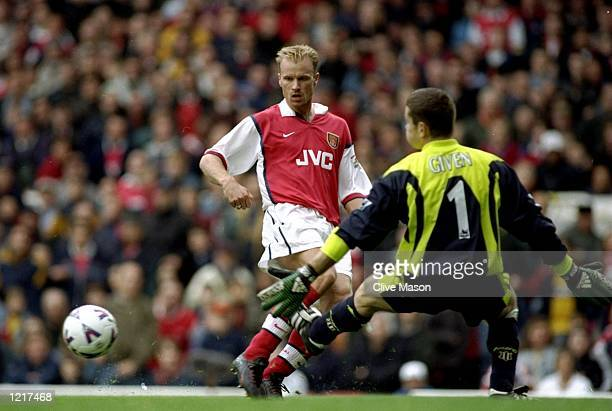 Dennis Bergkamp of Arsenal slots the ball past Shay Given of Newcastle United to score a goal during the FA Carling Premiership match against...