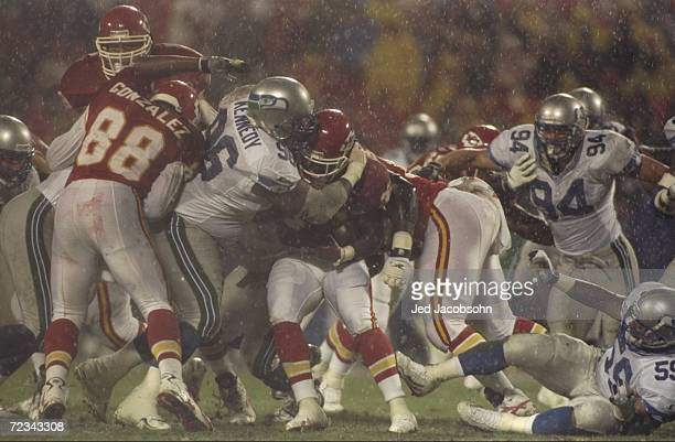 Runningback Donnell Bennett of the Kansas City Chiefs is tackled by Cortez Kennedy of the Seattle Seahawks during a game at the Arrowhead Stadium in...