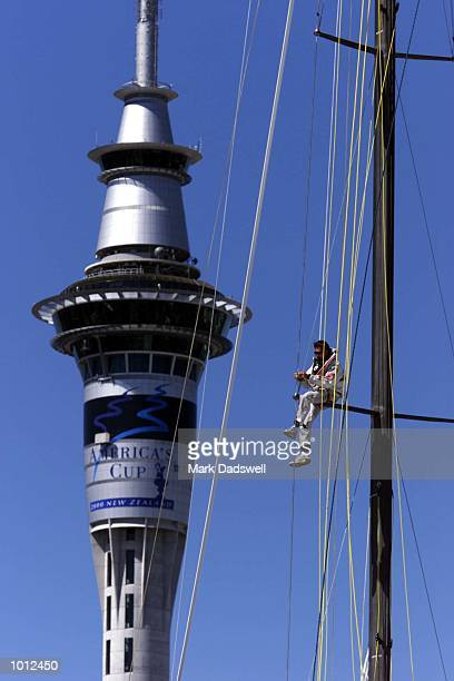 A crew member of Fast 2000 a Louis Vuitton Cup challenger from Club Nautique de Morges Switzerland works on the boats mast with the spectacular Sky...