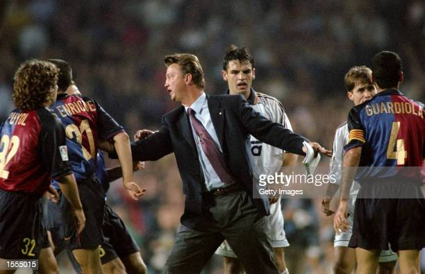 Barcelona coach Louis van Gaal calms his players down against Real Madrid during the Spanish Primera Liga match at the Nou Camp in Barcelona Spain...