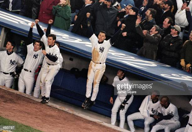 Derek Jeter of the New York Yankees celebrates in the dugout after Jim Leyrtiz hits a home run during the World Series Game four against the Atlanta...