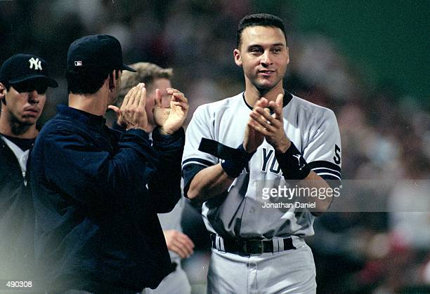Derek Jeter of the New York Yankees cheers during the ALCS game two against the Boston Red Sox at Fenway Park in Boston Massacusetts The Yankees...