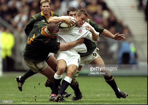 Jonny Wilkinson of England is tackled by Cobus Visagie and Joost van der Westhuizen of South Africa in the Rugby World Cup quarterfinal match at the...