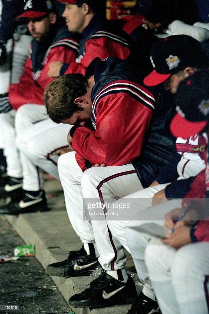 Kevin Millwood of the Atlanta Braves looks down as he sits in the dug out during the World Series game two against the New York Yankees at the Turner...