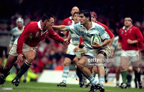 Octavio Bartolucci of Argentina hands off Mark Taylor of Wales during the opening Rugby World Cup Pool D match at the Millennium Stadium in Cardiff...