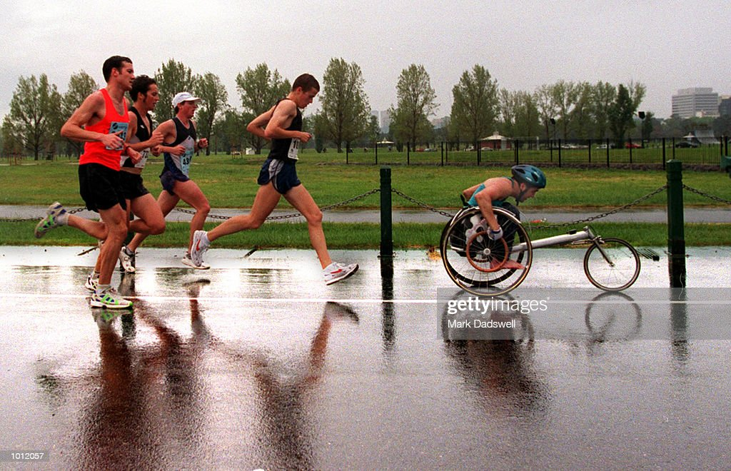 Runners and wheel chair competitors race through the rain during the first lap of the 1999 Melbourne Marathon, held at Albert Park, Melbourne, Victoria, Australia. Mandatory Credit: Mark Dadswell/ALLSPORT