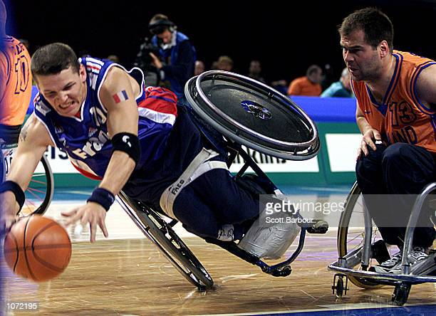 Frederic Guyot of France dives for the ball while Rene Martens of the Netherlands watches on during the Wheelchair Basketball match between France...
