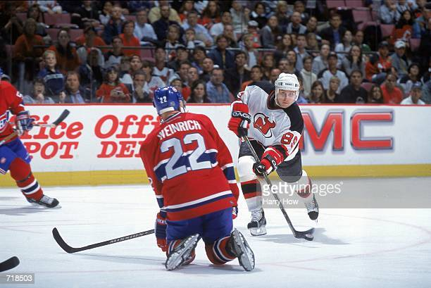 Alexander Mogilny of the New Jersey Devils moves the puck around Eric Weinrich of the Montreal Canadiens during the game at the Continental Airlines...