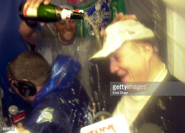 Derek Jeter of the New York Yankees pours champagne over the head of team owner George Steinbrenner in the locker room after the Yankees 42 win over...