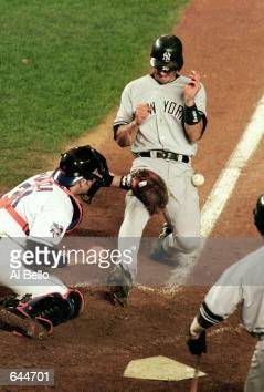 Jorge Posada of the New York Yankees scores the go ahead run as Catcher Mike Piazza of New York Mets gets ready to catch the ball at home plate...