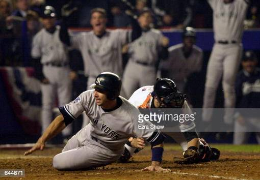 Jorge Posada of the New York Yankees slides past the tag of catcher Mike Piazza of the New York Mets to score the game winning run in the ninth...