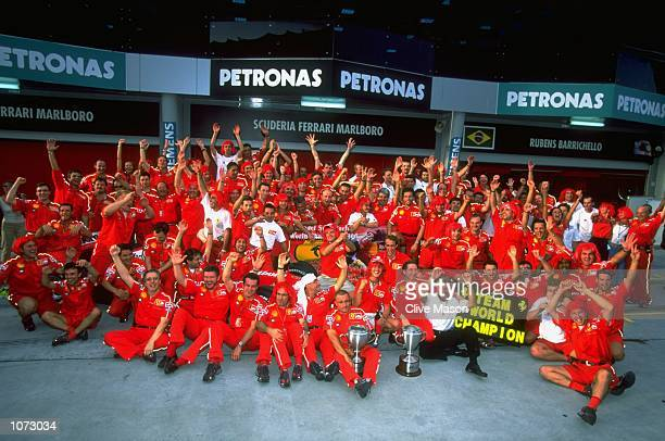 Michael Schumacher of Germany and Ferrari celebrates winning with the Ferrari team their two titles after the Malaysian Formula One Grand Prix at the...