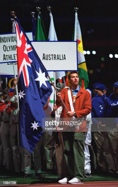 Swimmer Ian Thorpe of Australia carries the Southern Cross into the Olympic Stadium at the Closing Ceremony of the Sydney 2000 Olympic Games in...
