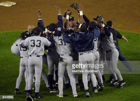 The New York Yankees mob pitcher Mariano Rivera after the last out is made against the New York Mets in Game 5 of the World Series at Shea Stadium in...