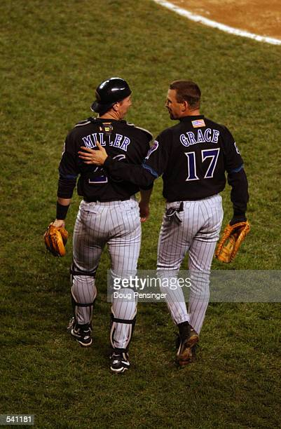 Catcher Damian Miller of the Arizona Diamondbacks and teammate Mark Grace walk on to the field during game 3 of the World Series against the New York...
