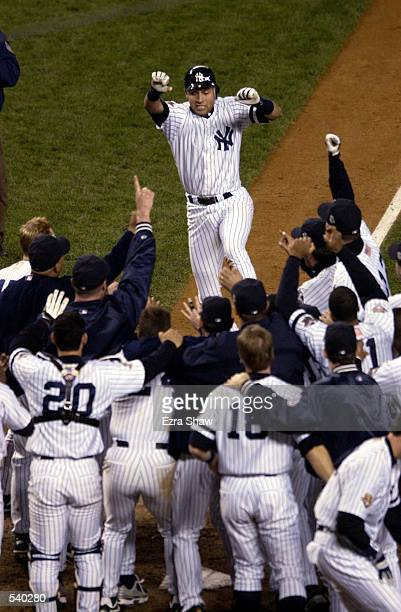 Derek Jeter of the New York Yankees celebrates his game winning home run in the 10th inning against the Arizona Diamondbacks during game four of the...