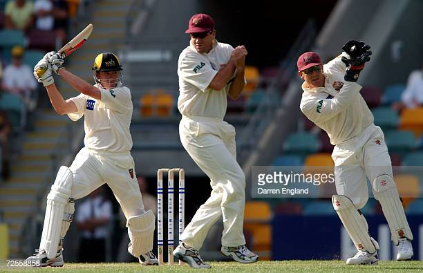 Marcus North of Western Australia hits four runs past Stuart Law and Wade Seccombe of Queensland during the Pura Cup cricket match between Queensland...