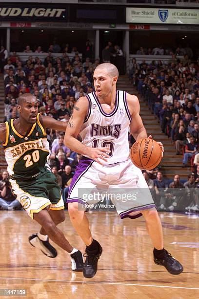 Mike Bibby of the Sacramento Kings looks to drive on Gary Payton during the Kings opening game versus the Seattle SuperSonics at the ARCO Arena in...