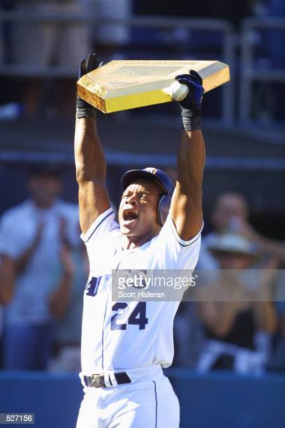 Rickey Henderson of the San Diego Padres holds a gold home plate after hitting a onerun home run in the third inning against the Los Angeles Dodgers...
