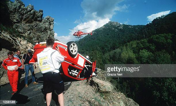 Tommi Makinen looks at the wreckage of his car as it lies on the edge of the road follwoing a crash during the Rally of Corsica a part of the World...