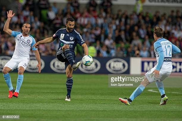 Fahid Ben Khalfallah of Melbourne Victory controls the ball in front of Manny Muscat of Melbourne City and Nick Fitzgerald of Melbourne City during...