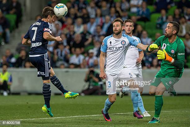 Marco Rojas of Melbourne Victory heads the ball towards goal in front of Josh Rose of Melbourne City and Dean Bouzanis of Melbourne City during the...