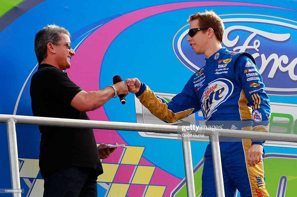 Octagon announcer Bruce Buffer (L) fist bumps Brad Keselowski, driver of the #2 Miller Lite Dodge, during driver introductions prior to the NASCAR Sprint Cup Series Ford EcoBoost 400 at Homestead-Miami Speedway on November 18, 2012 in Homestead, Florida.