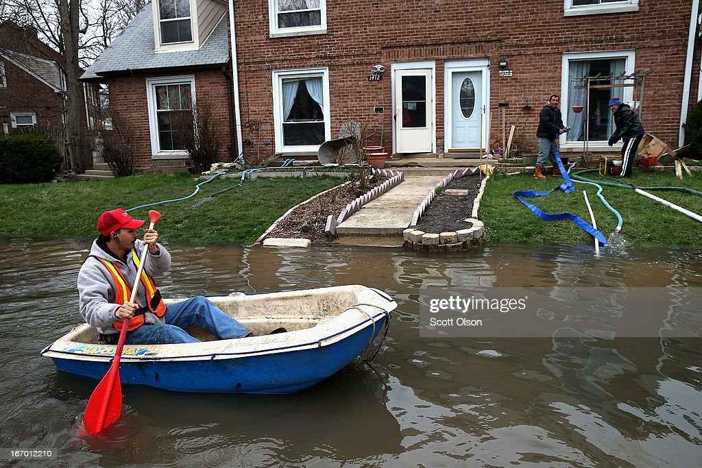 Octavio Castillo paddles a boat down a flooded street to reach the home of his cousin on April 19, 2013 in Des Plaines, Illinois. The suburban Chicago town is battling floodwater from the Des Plaines River which is expected to crest at a record 11 feet later today. Record-setting rains and rising rivers have caused wide-spread flooding in many Illinois communities.