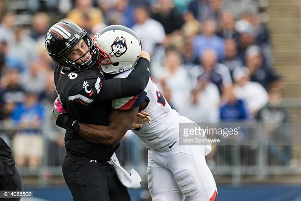 Cincinnati Quarterback Hayden Moore talks a hit from UConn Safety Obi Melifonwu during the second half of a NCAA football game between AAC rivals the...