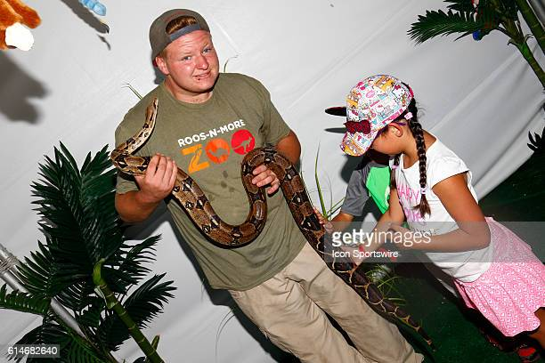 A volunteer from RoosNMore petting zoo lets children pet a redtailed boa constrictor during the 350 Fest in the Fan Engagement Area prior to the DC...