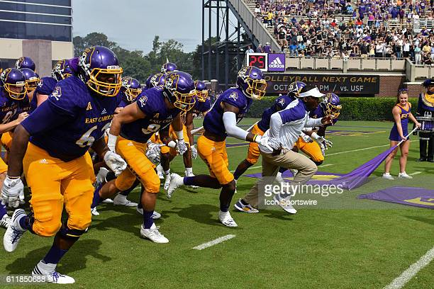 East Carolina head coach Scottie Montgomery leads his team out before a game between the East Carolina Pirates and the Central Florida Knights at...