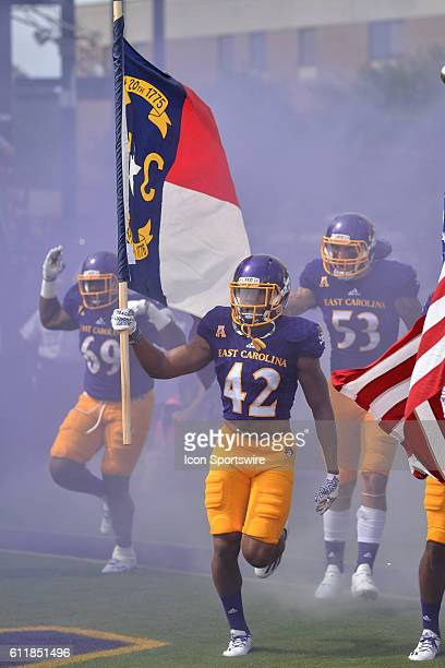 East Carolina Pirates defensive back Devon Sutton carries out the North Carolina flag before a game between the East Carolina Pirates and the Central...