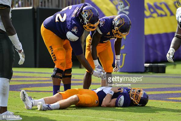 East Carolina Pirates running back Anthony Scott and offensive lineman Brandon Smith check on quarterback Philip Nelson after a targeting hit by UCF...
