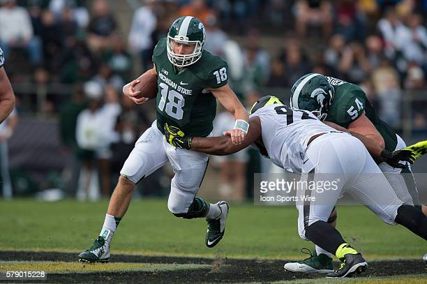 Michigan State Spartans quarterback Connor Cook runs by Purdue Boilermakers defensive tackle Ryan Watson during a football game between the Purdue...