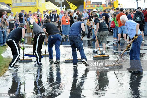 Workers push water from track hours before the Bank of America 500 at Charlotte Motor Speedway in ConcordNC